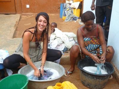 Frivillig hjelper lokal kvinne med oppvasken på et prosjekt i Togo