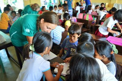 En frivillig assisterer elever på undervisningsprosjekt på Filippinene