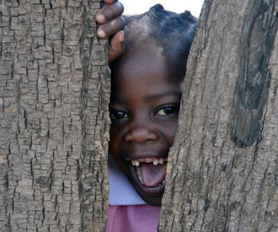 Jente på barnehjem i Tanzania titter gjennom et gjerde