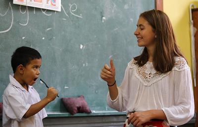 En frivillig viser en ung gutt hvordan man pusser tenner på en skole i Myanmar