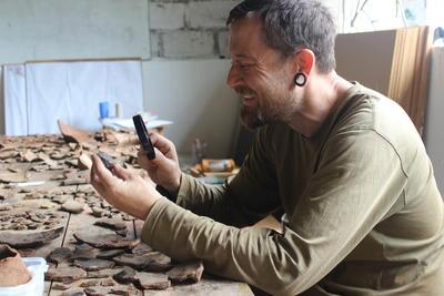 En frivillig studerer arkeologiske funn i Peru